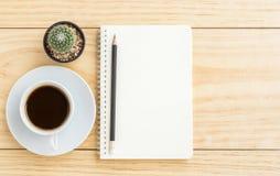 Kaffekopp, blyertspenna och anteckningsbok på trätabellen Royaltyfri Bild