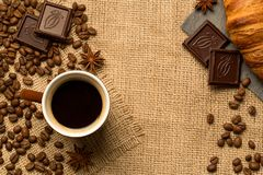 Kaffekopp, kaffebönor, choklad, giffel, kanel på säckväven Top beskådar arkivfoto