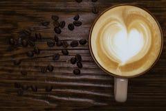 Kaffekopp, kaffebönor och bästa sikt för trätabell royaltyfria bilder