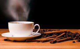 Kaffekopp, kaffebönor och kanelbruna pinnar på mörk bakgrund arkivbilder