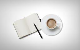 Kaffekopp med anmärkningsboken på tabellen Arkivbilder