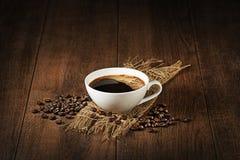 Kaffekopp med bönabakgrund Arkivbilder