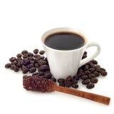 Kaffekopp med bönor och den kanelbruna pinnen för socker på vit Royaltyfria Bilder