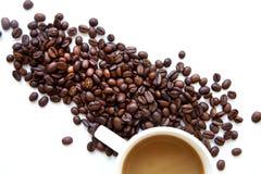 Kaffekopp med bönor som isoleras på vit bakgrund Arkivfoton
