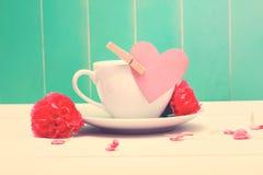 Kaffekopp med den rosa hjärtaetiketten och nejlikor royaltyfri bild