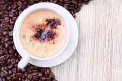 Kaffekopp med grillade kaffebönor Arkivbild