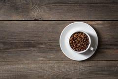 Kaffekopp med grillade kaffebönor på trätabellen Fotografering för Bildbyråer
