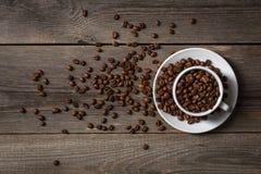 Kaffekopp med grillade kaffebönor på trätabellen Arkivfoton
