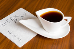Kaffekopp med handskriftveckaplan på servett Arkivbilder
