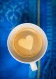 Kaffekopp med hjärtaform som göras av skum på den blåa kökshandduken arkivbild