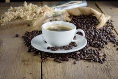 Kaffekopp med kaffebönor på den wood tabellen Fotografering för Bildbyråer