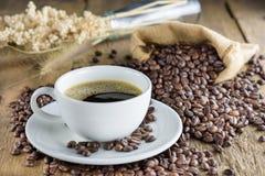 Kaffekopp med kaffebönor på den wood tabellen Arkivfoto