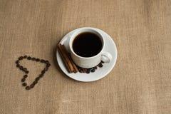Kaffekopp med kaffebönor på säckväv arkivfoton