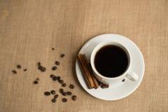 Kaffekopp med kaffebönor på säckväv royaltyfria bilder