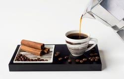Kaffekopp med kanel- och kaffebönor arkivbild