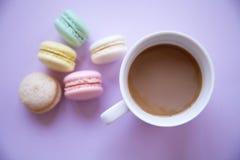 Kaffekopp med macaron på rosa bakgrund Arkivbild