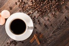 Kaffekopp med macarons och kaffebönor Royaltyfri Foto