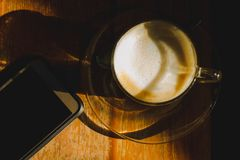 Kaffekopp med mobiltelefonen på kaffetabellen Royaltyfria Bilder