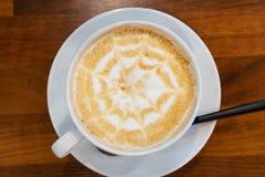 Kaffekopp med skum f?r stj?rnaformkonst p? tr?tabellbakgrund p? tabell?verkant p? kaf?t royaltyfria foton