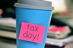 Kaffekopp med textskattdagen i kontoret Fotografering för Bildbyråer