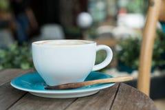 Kaffekopp med träskeden på tabellen i coffee shop på yttersidan Arkivfoto