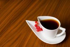 Kaffekopp med viburnumen på den bruna tabellen Royaltyfri Fotografi