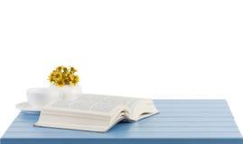 kaffekopp och öppnad bok på den blåa trätabellen royaltyfri bild