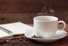 Kaffekopp och anmärkningsbok Arkivfoto