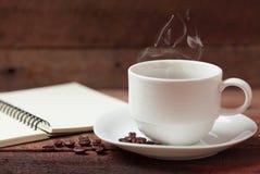 Kaffekopp och anmärkningsbok Arkivbild