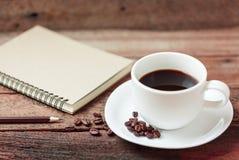 Kaffekopp och anmärkningsbok Arkivbilder