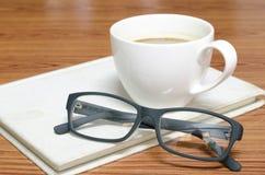 Kaffekopp och anteckningsbok med exponeringsglas Royaltyfri Fotografi
