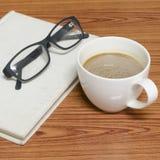 Kaffekopp och anteckningsbok med exponeringsglas Fotografering för Bildbyråer