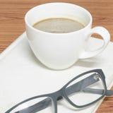 Kaffekopp och anteckningsbok med exponeringsglas Royaltyfria Bilder