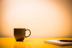 kaffekopp och anteckningsbok på tabellen med lampan på nattetid, vintag Fotografering för Bildbyråer