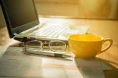 Kaffekopp och bärbar dator, diagram, monokel och penna royaltyfria bilder
