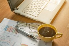Kaffekopp och bärbar dator, diagram, monokel och penna arkivbilder
