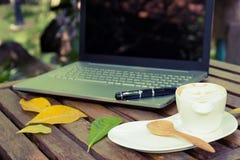 Kaffekopp och bärbar dator för affär Arkivfoton