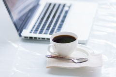 Kaffekopp och bärbar dator för affär Arkivfoto