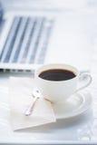Kaffekopp och bärbar dator för affär Fotografering för Bildbyråer