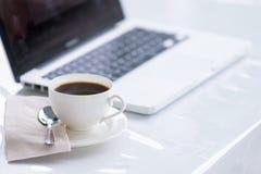Kaffekopp och bärbar dator för affär Arkivbilder