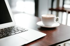 Kaffekopp och bärbar dator för affär på trätabellen i coffee shop i morgonen royaltyfri fotografi