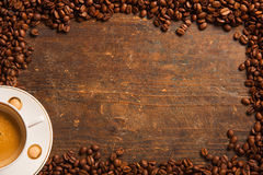 Kaffekopp och bönaram på trätabellen arkivbilder