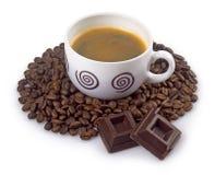 Kaffekopp och bönor med choklad på en vit bakgrund arkivfoto
