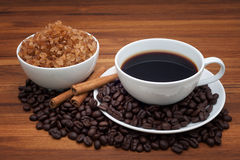 Kaffekopp och bönor på den wood tabellen Arkivbild
