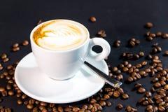 Kaffekopp och bönor på en svart bakgrund Arkivbild