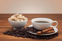 Kaffekopp och bönor på en trätabell Arkivfoton
