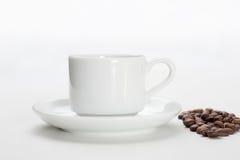 Kaffekopp och bönor på en vit bakgrund Royaltyfria Foton