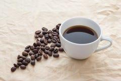 Kaffekopp och bönor på tabellen royaltyfria foton