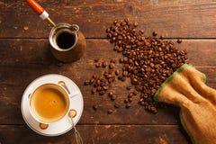 Kaffekopp och bönor på trätabellen royaltyfria foton