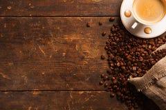 Kaffekopp och bönor på trätabellen royaltyfri bild